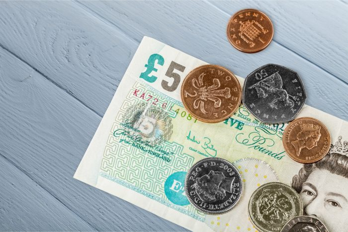 A five pound note and coins